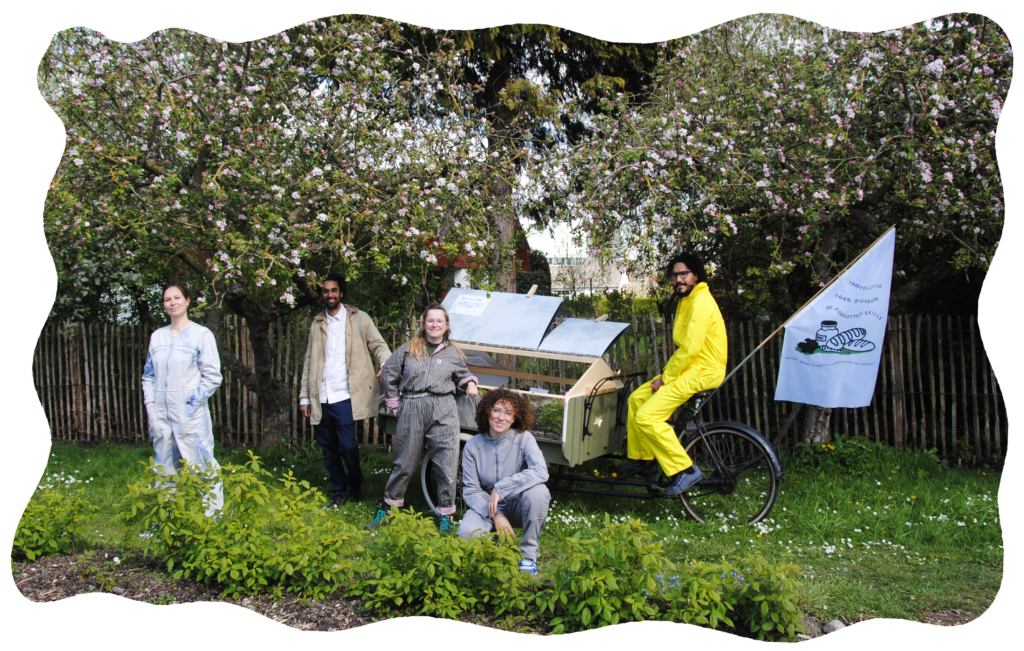 Image description: the team members of The Outsiders are posing in front of the Travelling Farm Museum bicycle underneath an apple tree.