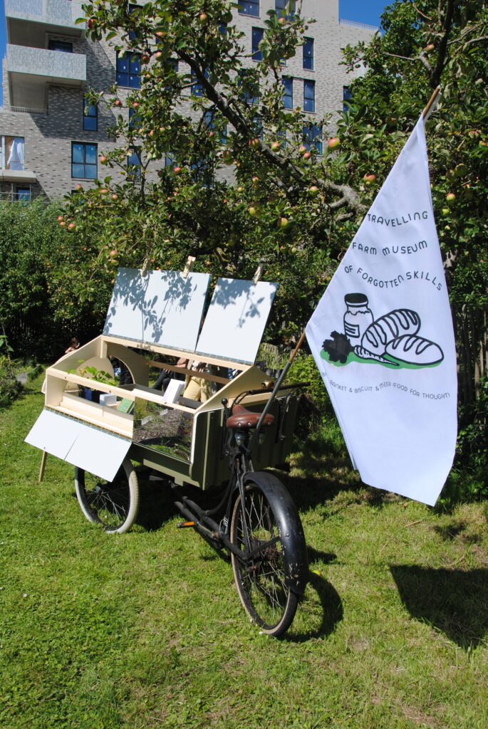Image description: the travelling farm bicycle is parked on some grass, it is open so the contents are visible and has the flag with the TFM logo.