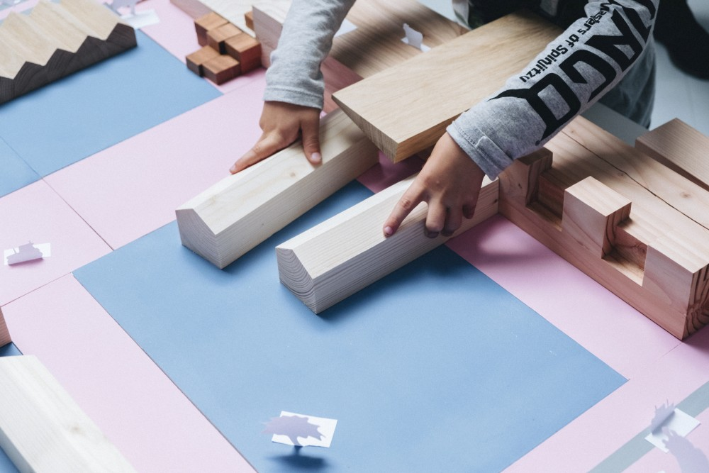 Image description: two hands of a child holds onto two wooden blocks that model the shape of a farmhouse over a painted surface with rectangular shapes.