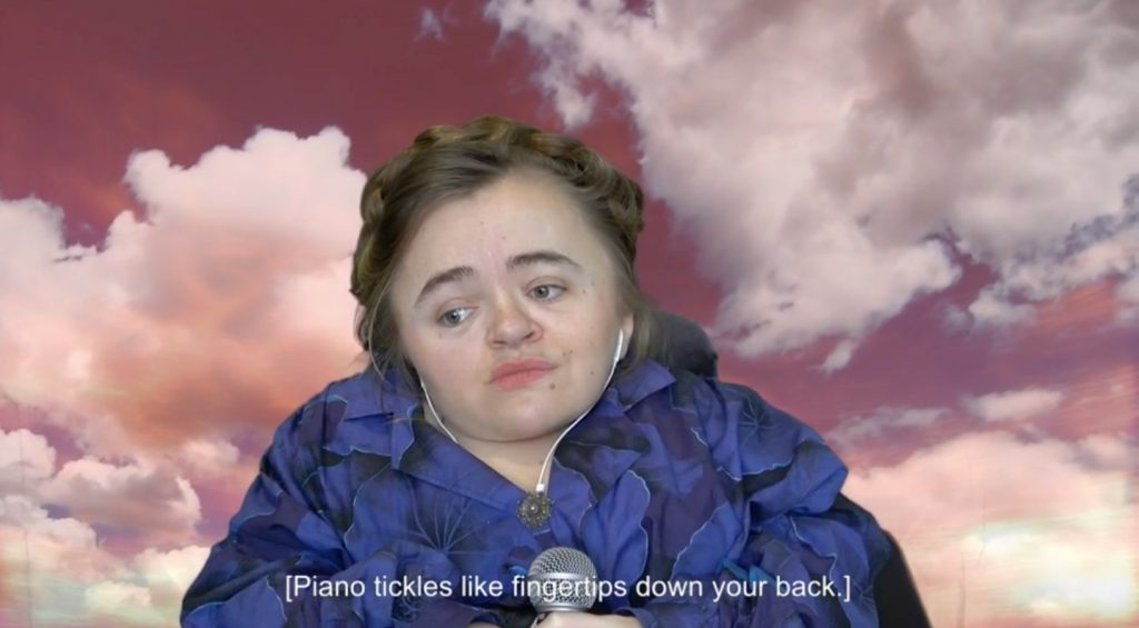 Image description: Mira Thompson holding a microphone in front of a sunset sky with captioned audio description that says [Piano tickles like fingertips down your back].