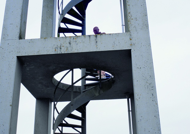 Image description: a view from below of a person standing on an outdoor spiral staircase encased by four cement pillars.