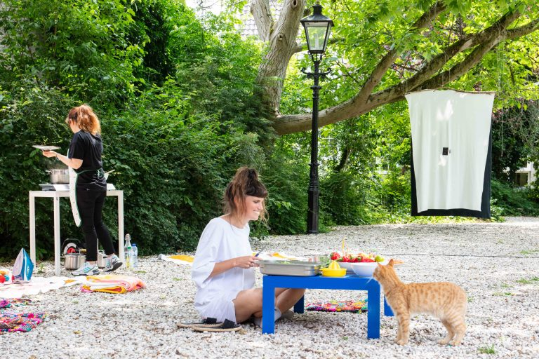 Image description: the nomadic installation in the courtyard at Casco with a cat, a woven cloth, various fabrics and the artists cooking and preparing vegetables; as well as a close-up of a wooden piece leaning against the planatus with text written in Farsi. Credit: Chun Yao Lin, photos, 2021.