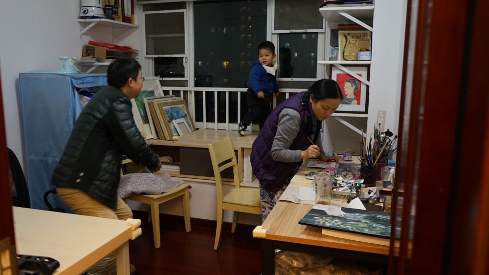 Image description: two adults and a child are busy in a room. One adult interacts with the child and the other is leaning over a table and painting.