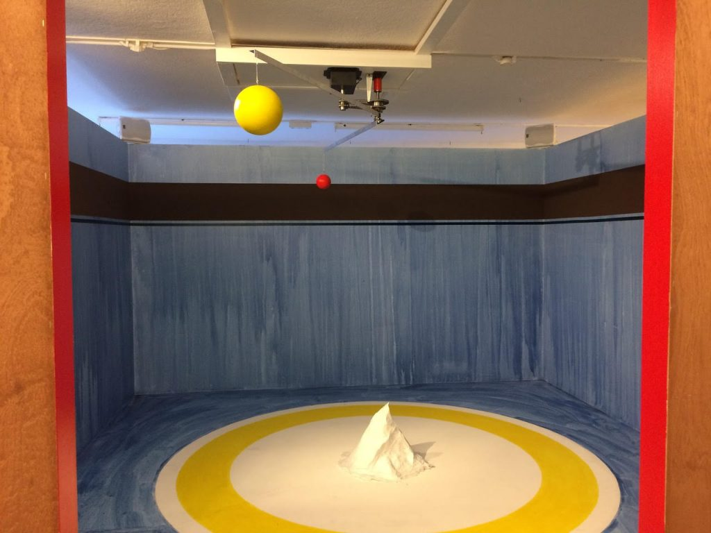 Image description: A small mountain features in the centre of a circle in a dynamic space with a rotating planetary system on the roof. Credit: Sara Sejin Chang (Sara van der Heide), The Mother Mountain Institute, kinetic sound installation, 2017-ongoing, photography the artist.