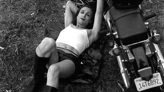 Image description: Terre Thaemlitz in 2000, white, non-essentialist trans person with a smirk on her face in a crop top, shorts, and knee high leather boots lying down on a jacket on the grass/dirt with one arm relaxed behind her head and the other touching the motorcycle that is parked next to her. Courtesy of Comatonse Recordings.