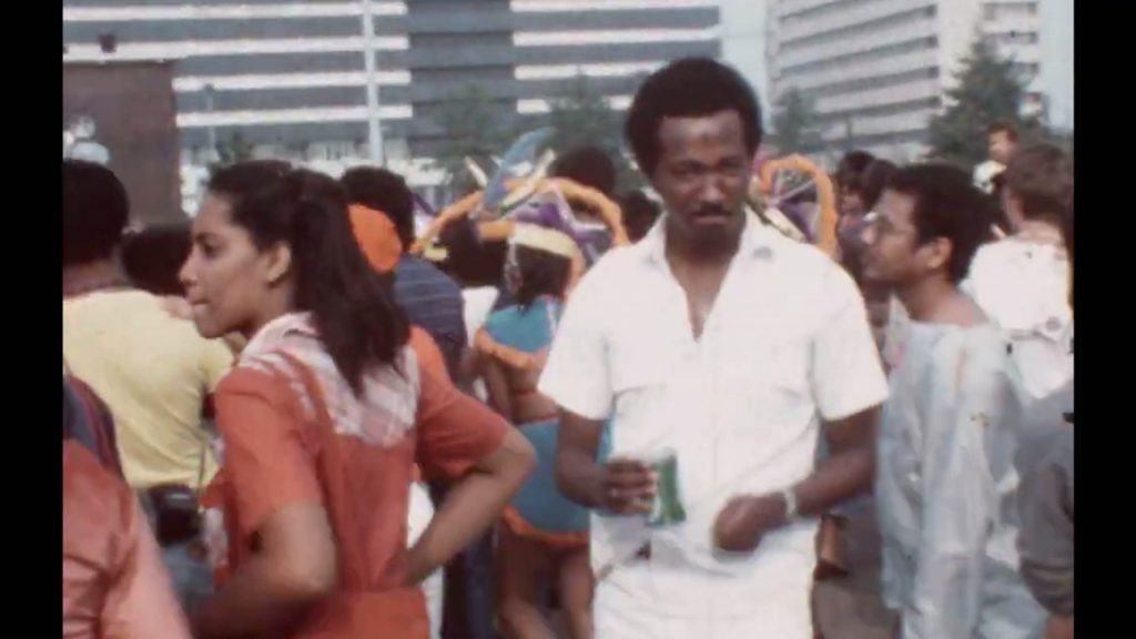 Image description: a person is facing the camera, holding a drink, while others are with their sides and backs towards us taking part in a parade. Credit: Film still from Carnival 1983 in Utrecht, and the author is Rudsel Martinus.